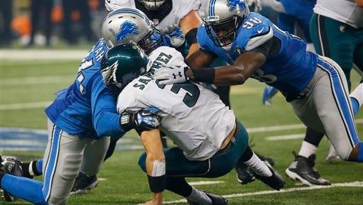 Eagles quarterback Mark Sanchez is sacked by Detroit Lions defensive end Ezekiel Ansah, left, and defensive end Devin Taylor (98) on Thursday. Sanchez was sacked six times.