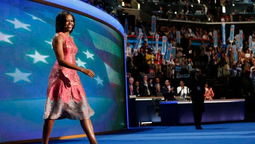 FILE - In this Sept. 4, 2012 file photo, first lady Michelle Obama, dressed in a Tracy Reese pink silk jaquard dress, walks on the stage at the Democratic National Convention in Charlotte, N.C. Reese, who hails from Detroit, is clearly one of the first lady's favored designers as Obama has been photographed in her clothes between 20 and 30 times.