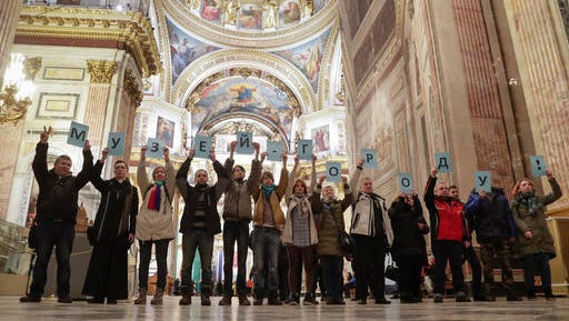Protesters against the transfer of St. Isaac's Cathedral to the Russian Orthodox Church hold a slogan 'The museum to the city!' standing inside the St. Isaac's Cathedral in St.Petersburg, Russia, Saturday, Jan. 28, 2017. Over 2,000 people rallied in St. Petersburg on Saturday to protest plans by the city authorities to give a landmark cathedral to the Russian Orthodox Church amid an increasingly passionate debate over the relationship between the church and state.