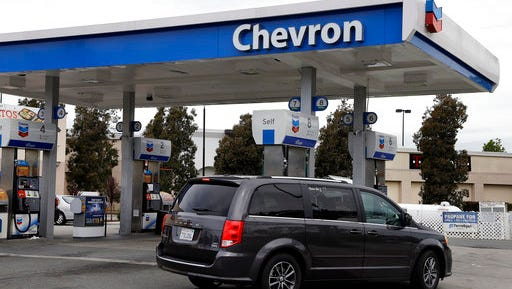In this Tuesday, April 25, 2017, photo, a motorist drives near the pumps at a Chevron gas station, in Oakland, Calif. According to the Energy Information Agency, the price of gasoline is 27 cents higher than this time last year.