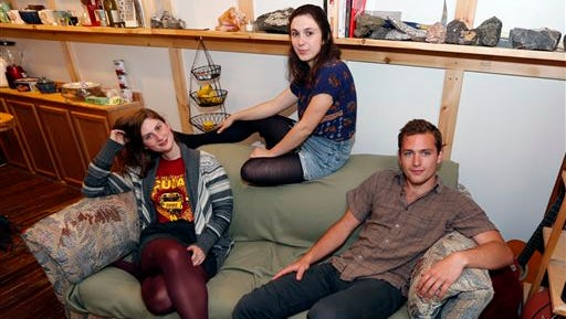 Lara Russo, left, Cally Guasti, center, and Reese Werkhoven sit on a couch in their apartment in New Paltz, N.Y. on Thursday, May 15, 2014. The roommates had purchased it at a Salvation Army store and found $40,800 stashed inside. After finding a deposit slip, they returned the money to the 91-year-old upstate New York widow who had hidden it there.