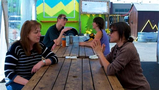 On Thursday, May 22, 2014,  people eat at Cartopia  in Portland, Ore. The Cartopia food cart pod in Southeast Portland is under a sale contract and likely to become an apartment building. It's the latest in a string of pods disappearing to make room for new construction.