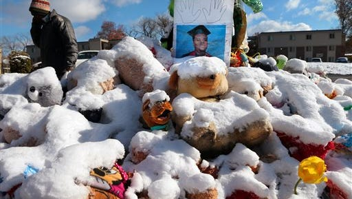 A high school graduation photo of Michael Brown rests on top of a snow-covered memorial Monday, Nov. 17, 2014, more than three months after the black teen was shot and killed nearby by a white policeman in Ferguson, Mo. The shooting sparked weeks of violent protests and  Missouri Governor Jay Nixon declaring a state of emergency today as a grand jury deliberates on whether to charge Ferguson police officer Darren Wilson in the death. (AP Photo/St. Louis Post-Dispatch, Robert Cohen)  EDWARDSVILLE INTELLIGENCER OUT; THE ALTON TELEGRAPH OUT