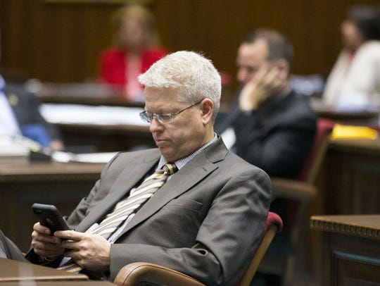 Rep. Eddie Farnsworth looks at his phone during a House