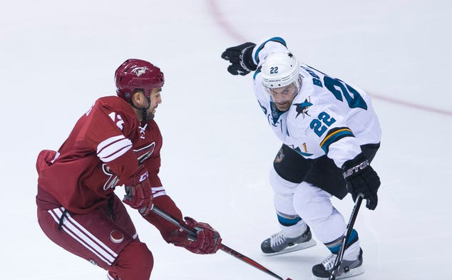 Coyotes' Paul Bissonnette skates past Sharks' Dan Boyle in the first period at Jobing.com Arena in Glendale, on Saturday, April 12, 2014.