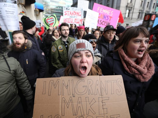 """A woman holds a sign that reads, """"Immigrants make US great"""". Thousands marched north from in Battery Park in lower Manhattan to speak up against an executive order banning non-U.S. citizens from seven countries in the Muslim world. Sunday, January 29, 2017"""