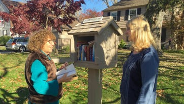 Judy Tyler meets one of the regular visitors to her little library in Cherry Hill, Maria Scocca.
