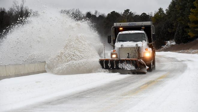 An Arkansas State Highway and Transportation Department plow removes snow Monday morning on the U.S. Highway 62 bridge over Norfork Lake in Henderson.