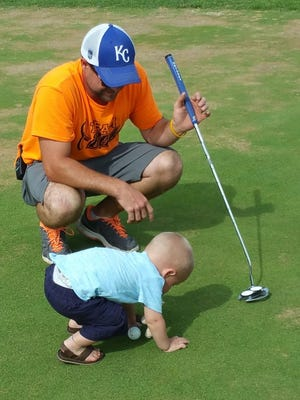 Chris Cazier kneels next to his son Blake Cazier while they golf during the first Team Blake Golf Tournament.