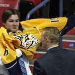 Thomas Novak puts on a sweater after being chosen 85th overall by the Predators during the third round Saturday.