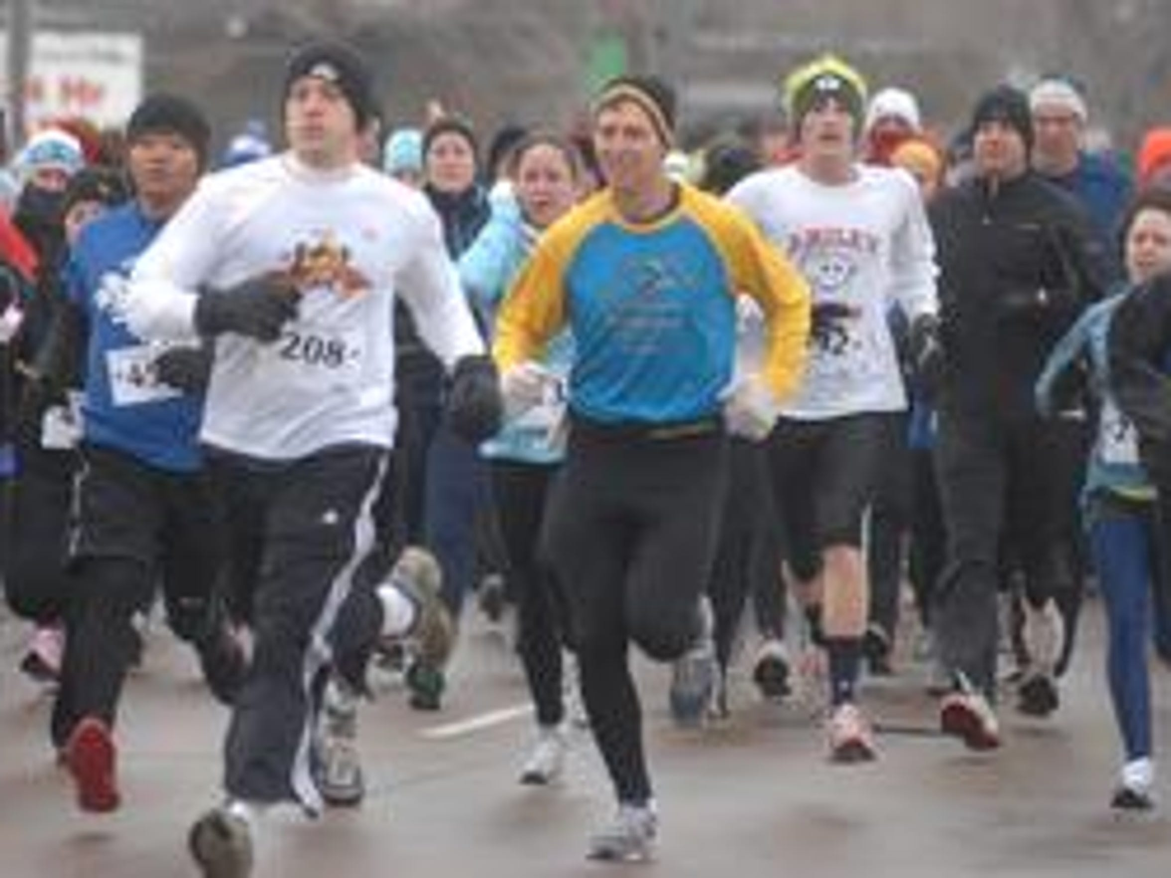Runners battle chilly weather as they run down First Avenue during the Eastbay Turkey Trot in Wausau.