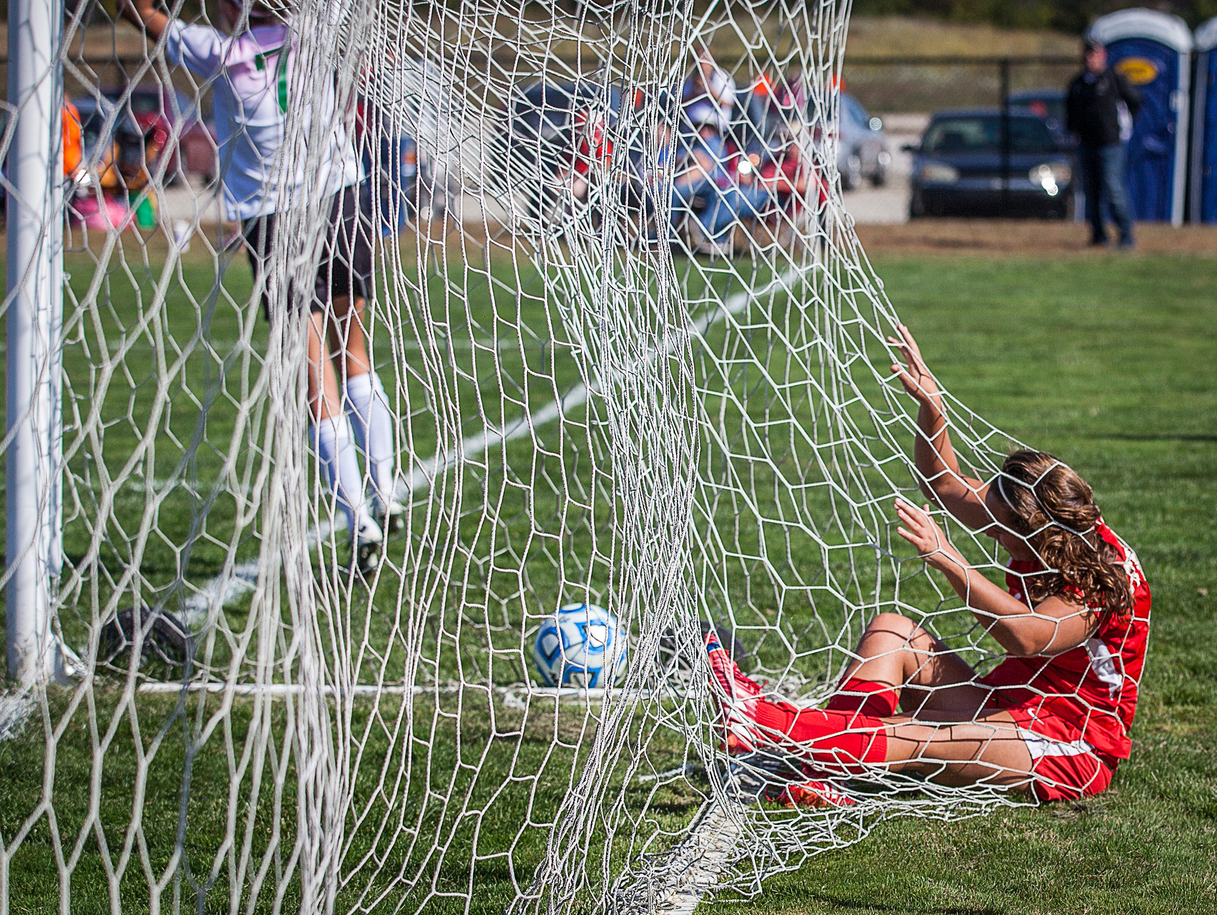 Jay County's Emily Muhlenkamp falls into the net after attempting to stop a goal made by Yorktown during their game at the Yorktown Sports Park on Saturday, Oct. 10, 2015.