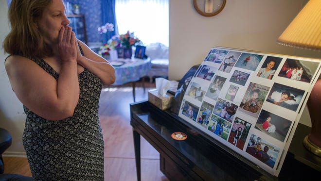 In this Wednesday, Sept. 2, 2015, photo, Dorothy McIntosh Shuemake, mother of Alison Shuemake, pauses as she looks at a picture collage of her daughter during an interview at her home, in Middletown, Ohio. Alison Shuemake, 18, died Aug. 26, after a suspected heroin overdose.