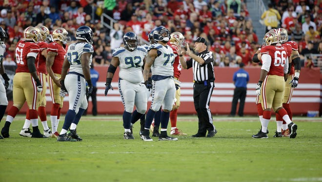 Seattle Seahawks defensive end Michael Bennett (72) reacts after sacking San Francisco 49ers quarterback Colin Kaepernick during the first half of an NFL football game in Santa Clara, Calif., Thursday, Oct. 22, 2015. Also pictured is defensive tackle Brandon Mebane (92).