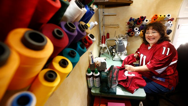 Patsy Elmer makes alterations to Carson Palmer's game jersey on Jan. 20, 2016 in Phoenix, Ariz. Patsy Elmer is the seamstress responsible for altering and hand-stitching numbers and names on the Arizona Cardinals' jerseys from her home-office.