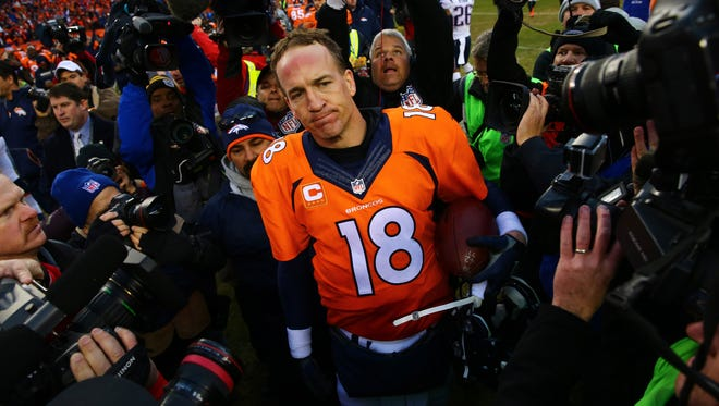 Denver Broncos quarterback Peyton Manning (18) reacts as he is surrounded by photographers following the game against the New England Patriots in the AFC Championship Game at Sports Authority Field at Mile High.