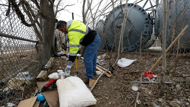 Jose Marrero with the City of Des Moines' property clean-up unit discards items left behind Wednesday, March 23, 2016, as crews clear out a homeless camp site near the intersection of Southwest 11th Street and Martin Luther King Parkway in Des Moines.