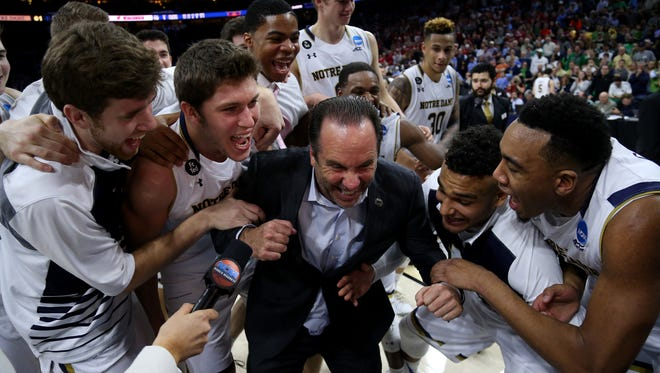 Notre Dame coach Mike Brey celebrates with his team after defeating the Wisconsin Badgers to reach the Sweet 16.
