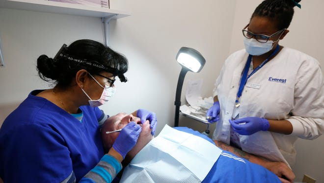 Don Wolf has dental work done by dentist Carmen Brumley, left, and Everest student Tarrah Lawrence on Friday, Apr. 8, 2016 at the Lift Up Springfield medical and dental clinic.
