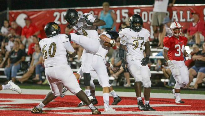Warren Central's Michael Tutsie, center, celebrates with team mates in the end zone after catching an interception and scoring during the first game of the season, as Warren Central High School takes on Center Grove High School at Center Grove, Friday August 19th, 2016.