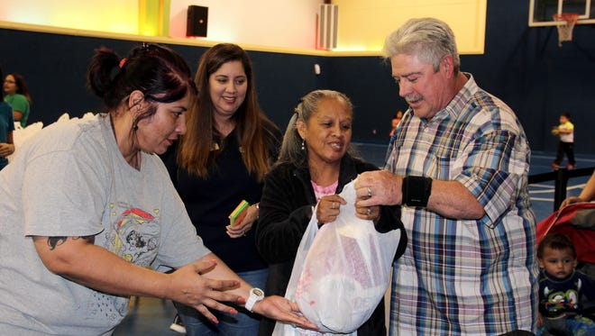 Diana Salazar, left, and Joy Jaramillo give a turkey and side dishes to Yolanda and Kenneth Fry.