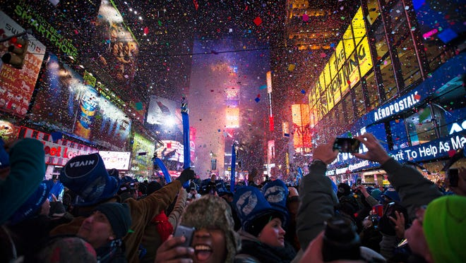 This Jan. 1, 2014, file photo shows revelers cheering under falling confetti at the stroke of midnight during the New Year's Eve celebrations in Times Square, in New York.