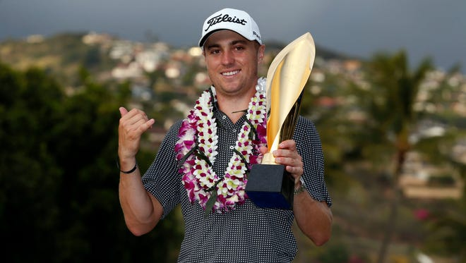 PGA golfer Justin Thomas poses with the trophy after winning the Sony Open golf tournament at Waialae Country Club.