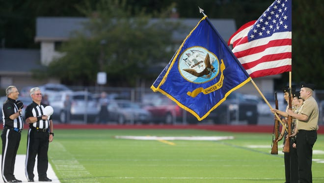 The South Kitsap NJROTC displays the flags during the playing of the national anthem before Friday's football game against Olympia.