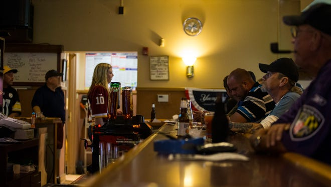 Patrons at the American Legion Walter L. Fox Post #2 watch various NFL games Sunday in Dover. NFL viewership the post has dropped significantly since players began taking a knee in protest during the national anthem. The change has hurt the post's income greatly.