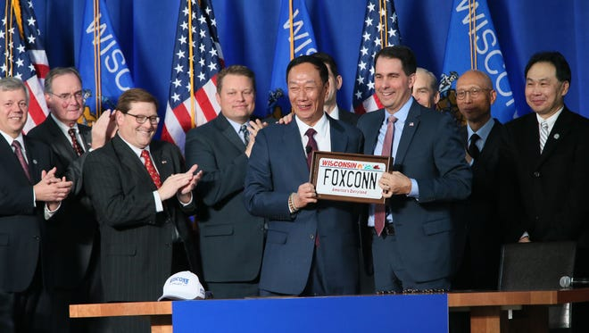 Terry Gou (center), chairman of Foxconn, gets a custom Wisconsin license plate presented to him by Gov. Scott Walker.