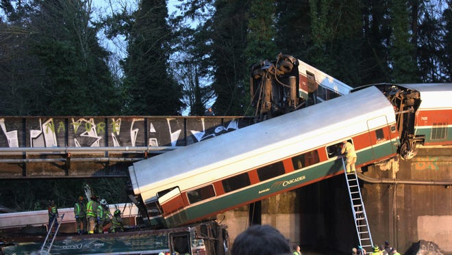 In this photo provided by Daniella Fenelon, first responders work at the scene of an Amtrak train that derailed south of Seattle on Monday, Dec. 18, 2017.
