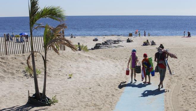 Beachgoers head down to the beach at Sea Bright.
