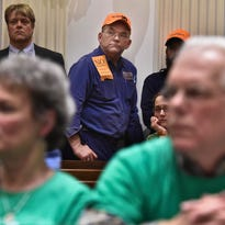 A bill opponent is framed by bill supporters during a public meeting on a proposed bill that would expand background checks for gun sales at the Statehouse in Montpelier on Tuesday, February 10, 2015. Opponents of the bill wore orange while supporters wore green.