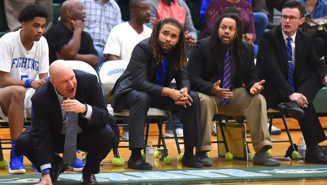 Robert E. Lee assistant coaches Terrell Mickens, Teley Tate and Sam LaClair remain seated as head coach Jarrett Hatcher reacts to an official's call on the court during the Region 2A East championship game played in Mechanicsville on Feb. 25, 2017.