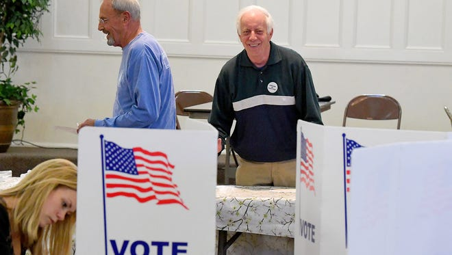 Officer of Election Charlie Hildebrand (right) directs another voter to a voting booth at the Ward 5 polling place in Staunton on Tuesday, May 1, 2018.