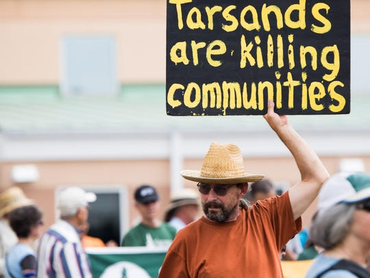 Dave Winkler holds his sign in protest against tar sands oil at the Remember the Kalamazoo rally on Saturday.