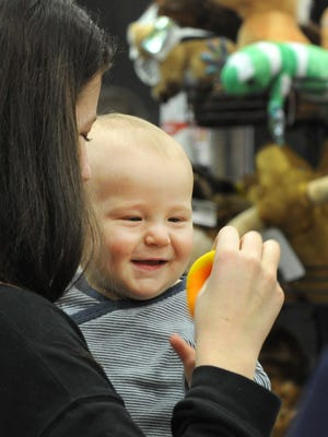 A mother and her infant child look at toys at one of several vendor booths at the Ray Clymer Exhibit Hall Friday morning during the Junior League of Wichita Falls' 36th annual Christmas Magic.