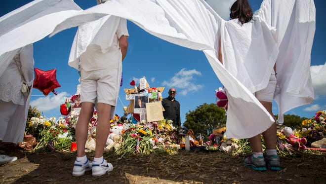 """Courtney Mark, 56, pays his respects at the memorials set up outside of Marjory Stoneman Douglas High School during back to school orientation day in Parkland on Sunday, Feb. 25, 2018. """"It's too close to home not to come,"""" said Mark. """"These could have been our kids."""""""