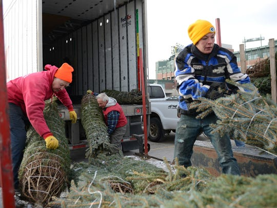 Ron Tillman, of Tillman Trees, left, Jon Bigler, of Rolling Hills Tree Farm, center, and Heather Roach, of North Countree Christmas, help load a FedEx truck with donated Christmas trees for the Trees for Troops program, at the Lambeau Field parking lot, Tuesday, December 2, 2014.