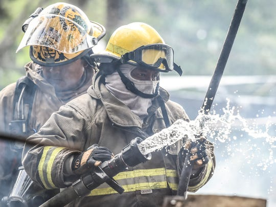Guam Fire Department firefighters Cliff Cruz, left, and Mancini Santos, extinguish the remains of a wood and tin structure fire near Pago Bay on Feb. 16. A resident was able to escape the fire and there were no injuries, according to GFD Spokesman Kevin Reilly.