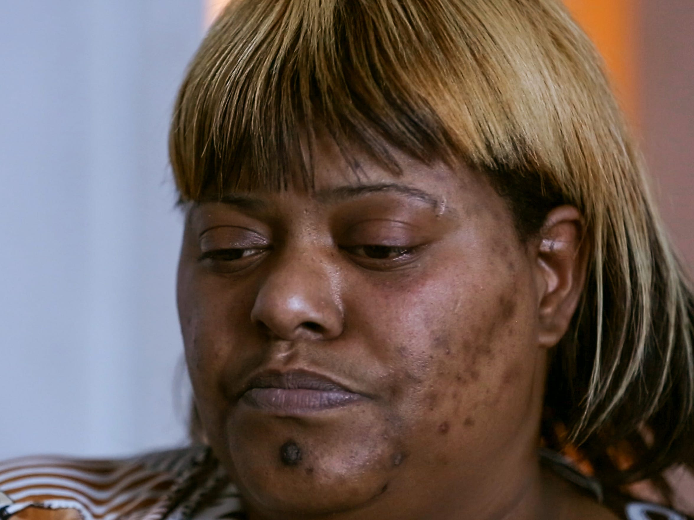 Seretha Edwards sits on a couch in her home discussing
