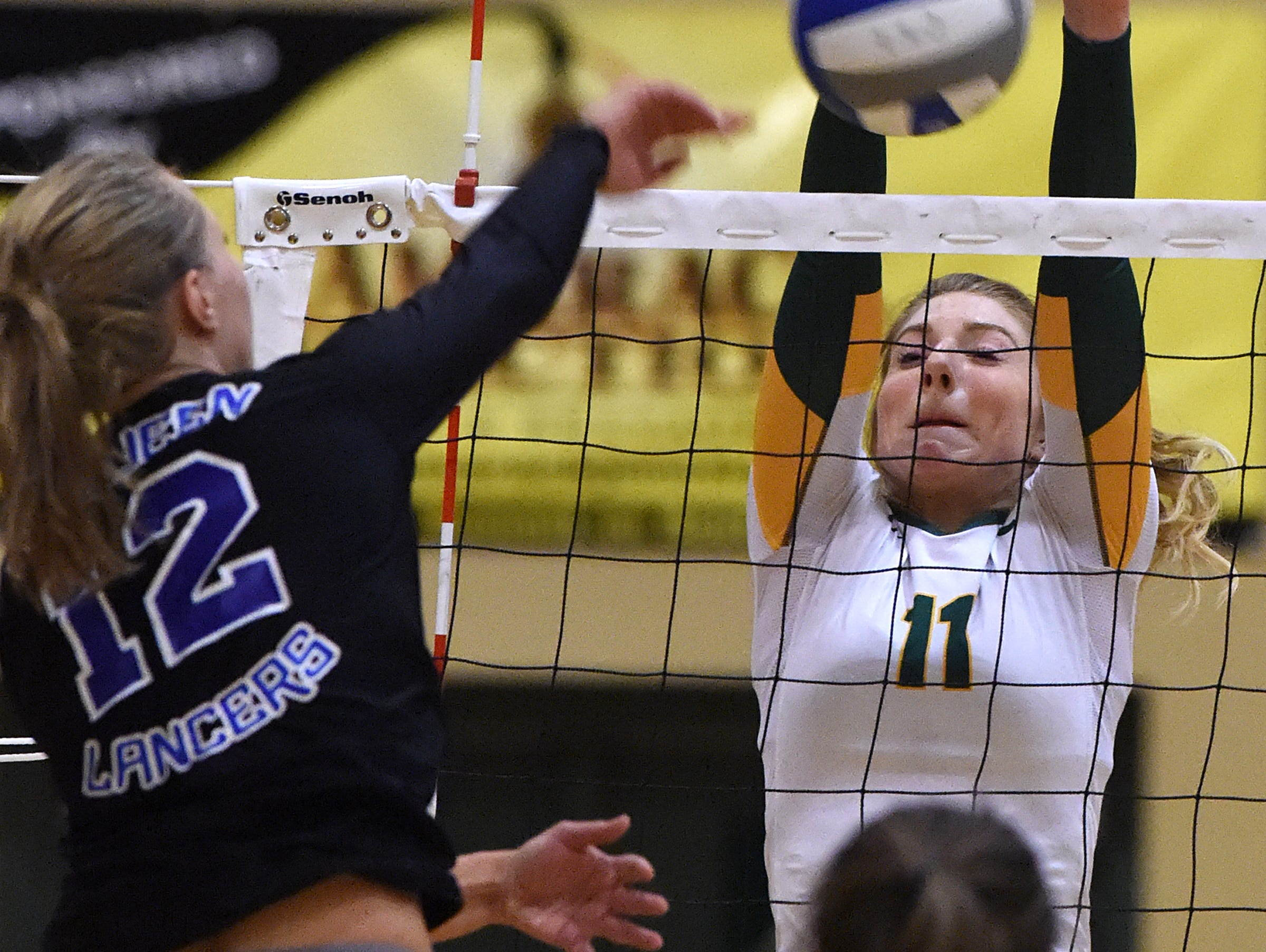 Manogue's Becca Smith goes up to block a shot by McQueen's Annika Kerns during Tuesday's game at Manogue High School on Sept. 20, 2016.