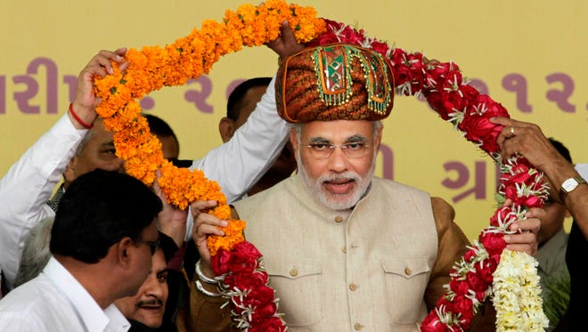 Gujarat state Chief Minister and India's main opposition Bharatiya Janata Party leader Narendra Modi receives a garland during his fast for communal harmony in Godhra, India.