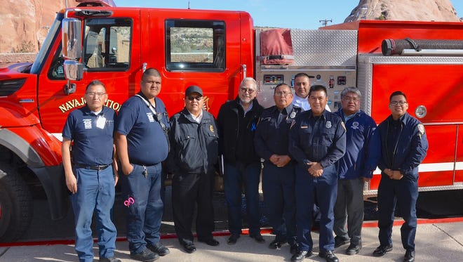 Navajo Nation Department of Fire and Rescue Services personnel stand with Delegate Benjamin Bennett, fourth from left, and Division of Public Safety Executive Director Jesse Delmar, second from right, at the Navajo Nation Council chamber on Thursday in Window Rock, Ariz.