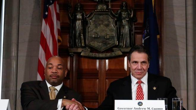 Assembly Speaker Carl Heastie, D-Bronx, left, and New York Gov. Andrew Cuomo shake hands during a news conference in the Red Room at the Capitol on March 18.