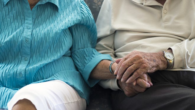 Fred Meserall, right, holds hands with his wife, Betty Meserall, in August as they reflect on stories of the past.