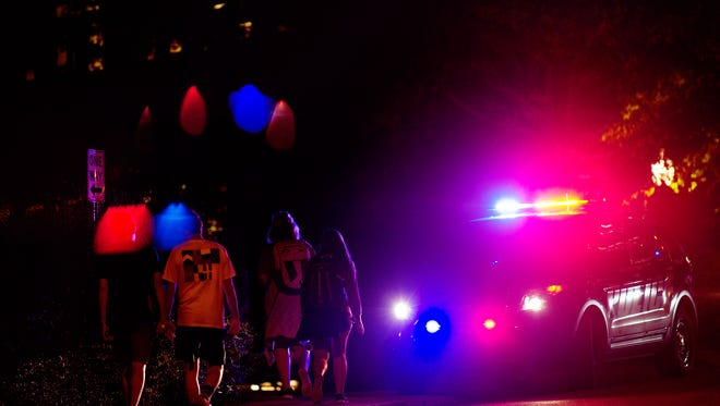 Students pass by a police car responding to a fire inside Massey Hall on the UTK campus in Knoxville, Tennessee, on Sunday, September 24, 2017.