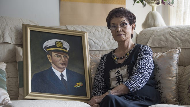 Tadako Knight, widow of WWII veteran Tommy Knight, holds an oil painting of her late husband that she painted in their home Friday, Oct. 7, 2016.