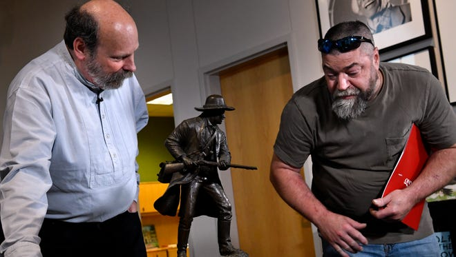 Richard Bruce Winders, the director of Education and Curation at the Alamo (left) looks over the bronze Alamo fighter statue brought by Shane Stapleton to the National Center for Children's Illustrated Literature Thursday April 12, 2018. Stapleton said he found the statue in a garbage pile and brought it to the Alamo Roadshow at the NCCIL to learn more about it. Officials were presenting the Alamo Roadshow, a nine-city tour educating the public on changes to be made to the iconic Texas landmark.