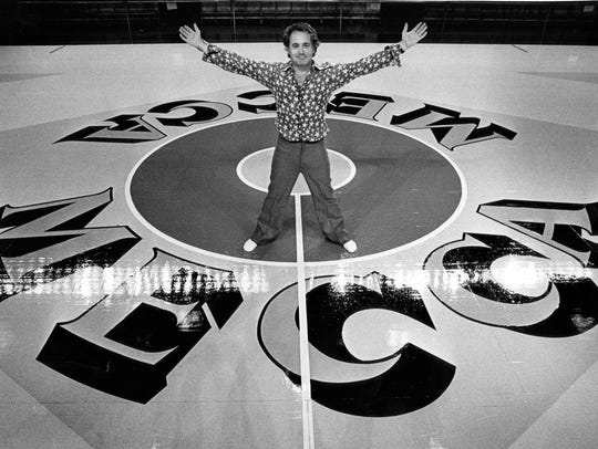 Robert Indiana, artist, poses with the Mecca floor